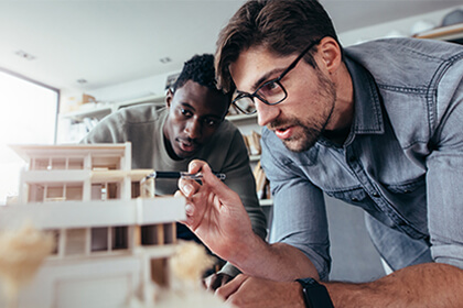 Two men working on a model building