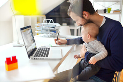 A man with a child in his arms looking at a computer