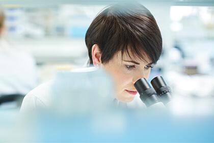 Woman looing through a microscope